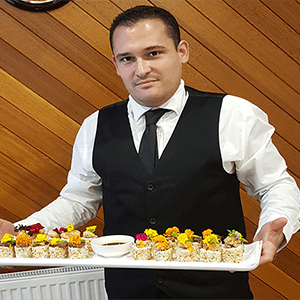 waiter serves sushi finger food canape catering service